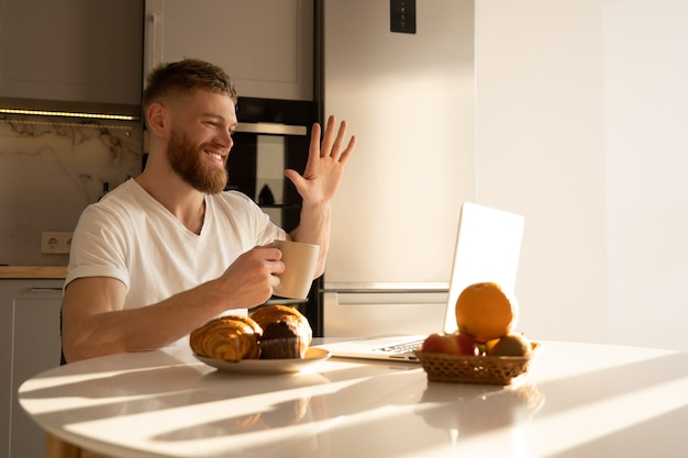 Young man waving hand to laptop computer and drinking tea or coffee. smiling european bearded guy sitting at table with food and have video call. interior of kitchen in modern apartment. sunny morning