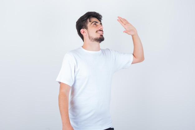 Young man waving hand to say goodbye in t-shirt and looking joyful