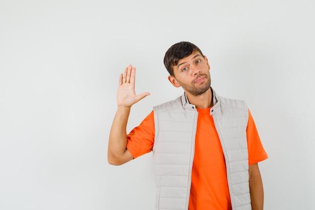 Молодой человек машет рукой, чтобы попрощаться в футболке, куртке