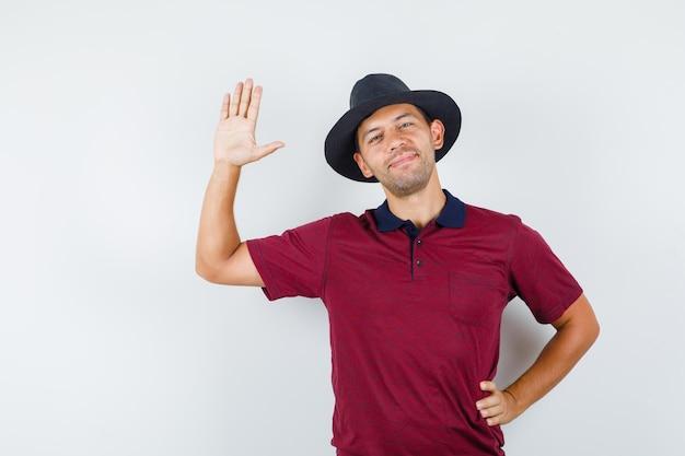Молодой человек машет ладонью, чтобы поздороваться в футболке, шляпе и выглядит радостным, вид спереди.