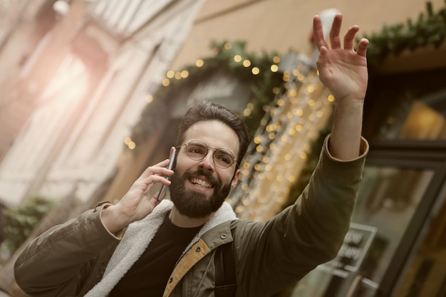 Young man waving on the street and talking on the phone