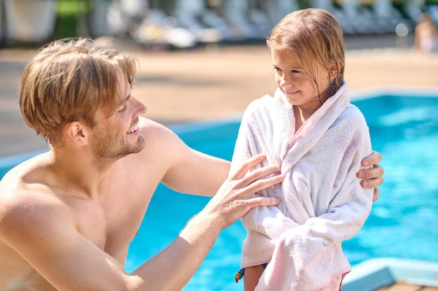 A young man wdrying his kid with a towel near the pool