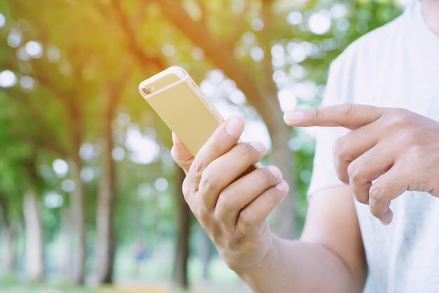 젊은 남자는 격자 무늬 셔츠를 입는다. 소파에 휴식하는 동안 휴대 전화를 사용하여 손을 닫습니다. 휴식 시간 동안 모바일 스마트 폰에서 메시지를보고 앉아 휴식. 소프트 포커스.