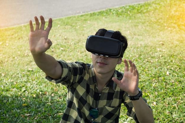 Молодой человек носить гарнитуру виртуальной реальности в саду