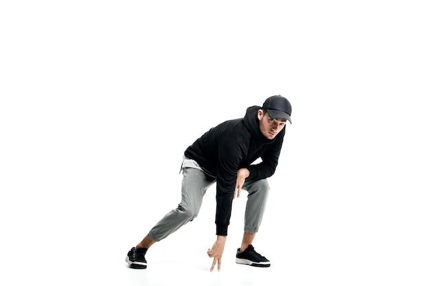 黒のスウェットシャツ、灰色のズボン、帽子、白い背景の上のストリートダンスを踊るスニーカーを身に着けている若い男
