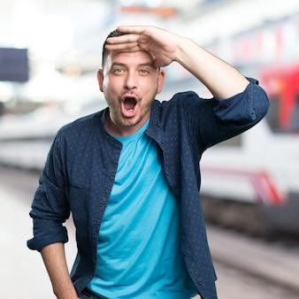 青い服を着ている若い男。驚い探しています。