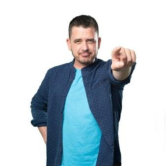 파란색 옷을 입고 젊은 남자. 손가락으로 가리키는.
