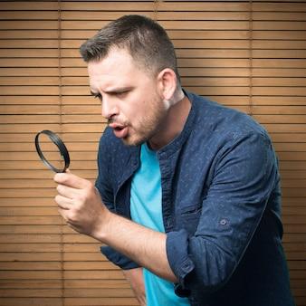 파란색 옷을 입고 젊은 남자. 돋보기 사용.