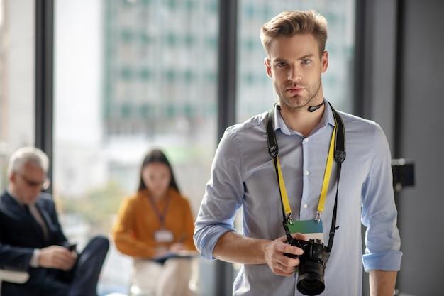 Молодой человек в синей рубашке держит камеру, стоя в студии