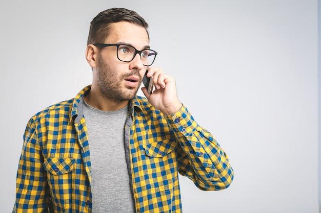 Молодой человек в повседневной рубашке и очках с помощью телефона