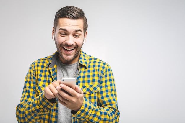 Молодой человек в повседневной рубашке с помощью телефона