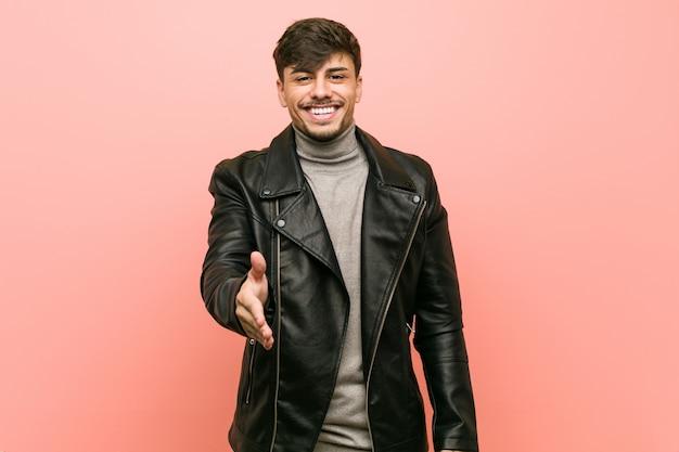 ジェスチャーの挨拶でカメラに手を伸ばして革のジャケットを着ている若い男