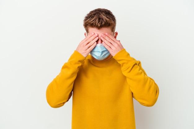 Молодой человек в маске от коронавируса на белом фоне прикрывает глаза руками, широко улыбается в ожидании сюрприза.