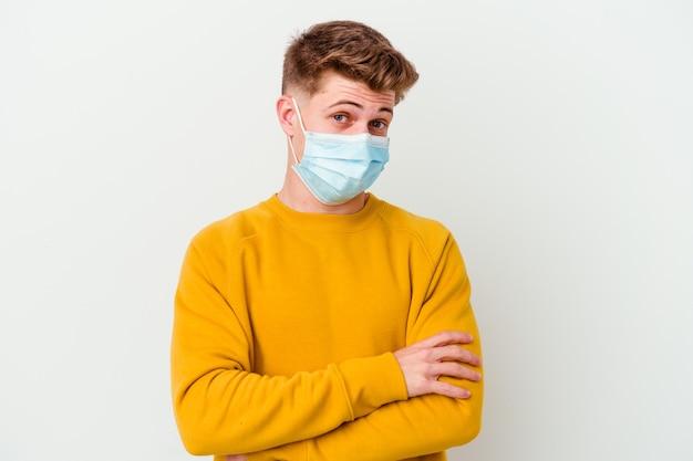 Молодой человек в маске от коронавируса на белом фоне недоволен, глядя в камеру с саркастическим выражением лица.