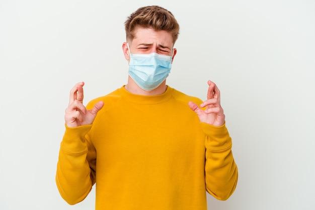 행운을 갖는 흰 벽 횡단 손가락에 고립 된 코로나 바이러스 마스크를 쓰고 젊은 남자