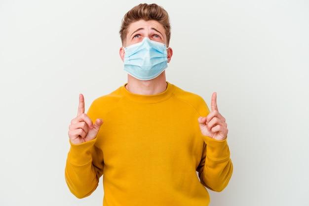 口を開けて逆さまを指している白い壁に分離されたコロナウイルスのマスクを身に着けている若い男