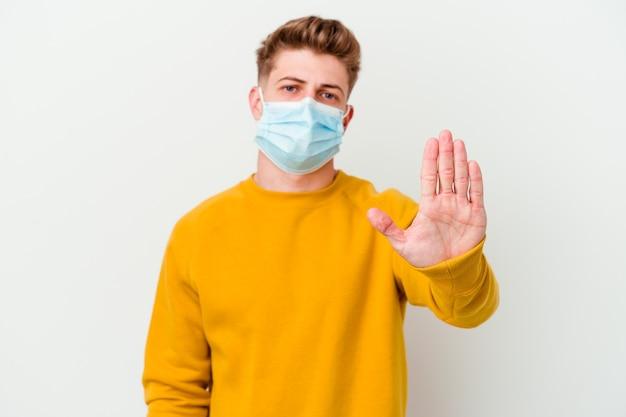 白い壁に隔離されたコロナウイルスのマスクを身に着けている若い男が一時停止の標識を示している手を伸ばして立って、あなたを防ぎます