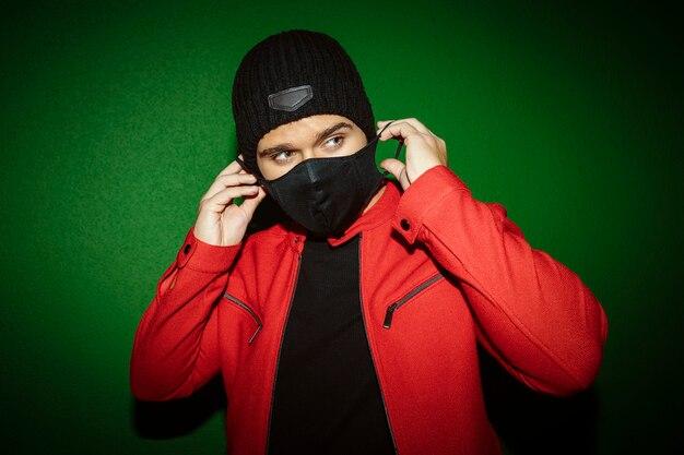 거리의 녹색 벽 배경에 마스크를 쓰고 젊은 남자. 영과 패션 개념.