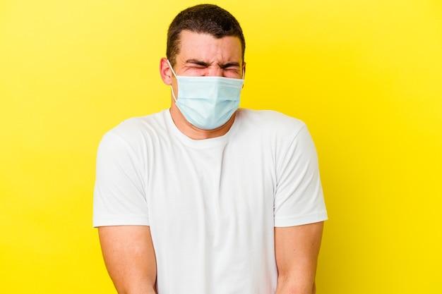 黄色の壁に分離されたコロナウイルスの保護を身に着けている若い男は笑って目を閉じ、リラックスして幸せを感じます
