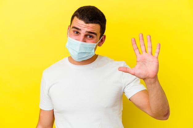 黄色の壁に分離されたコロナウイルスの保護を身に着けている若い男は、指で5番目を示す陽気な笑顔