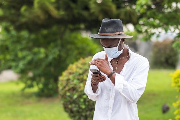 屋外で彼の電話を使用して保護フェイスマスクを身に着けている若い男