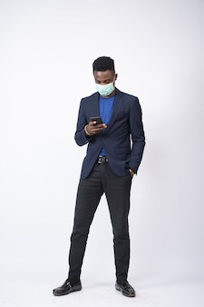 Молодой человек в костюме и маске, используя свой мобильный телефон