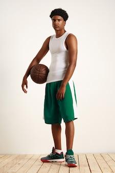 Молодой человек в белой рубашке, повязке на голову, зеленых шортах и зеленых кроссовках стоит со старым кожаным баскетбольным мячом под мышкой