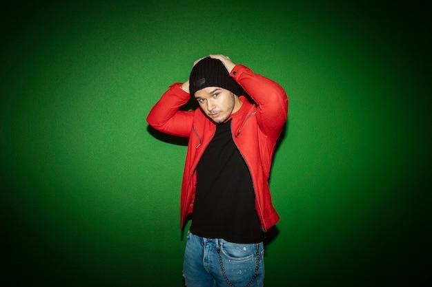 거리의 녹색 벽 배경에 모직 모자를 쓰고 젊은 남자. 영과 패션 개념. copyspace와 이미지