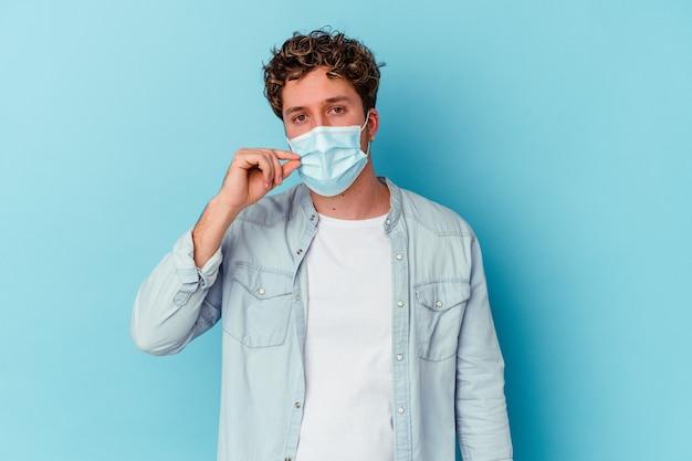 비밀을 유지하는 입술에 손가락으로 파란색 벽에 고립 된 항 바이러스 마스크를 착용하는 젊은 남자