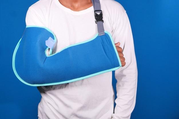 Молодой человек носить скрепку для сломанной руки.