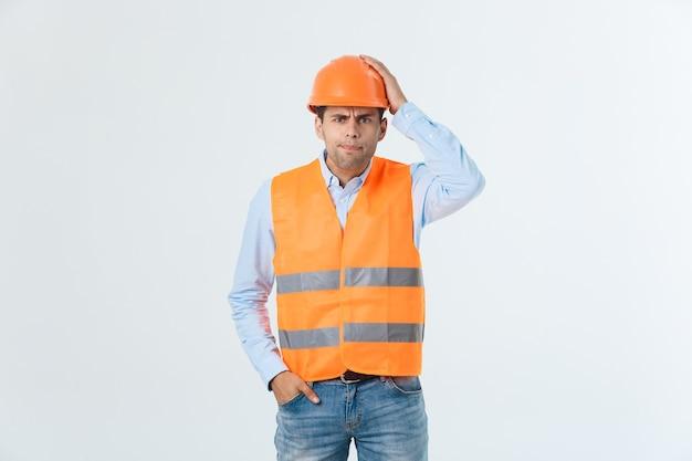 怒った顔、否定的な嫌いな感情を持つ建築家の衣装とヘルメットを身に着けている若い男。怒りと拒絶の概念。