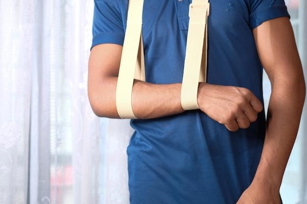 Young man wearing an arm brace for broken hand .