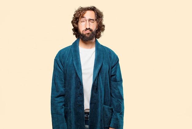 Young man wearing bathrobe night suit boring