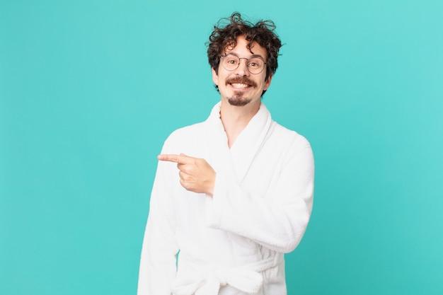유쾌하게 웃고, 행복감을 느끼고 측면을 가리키는 목욕 가운을 입은 젊은 남자