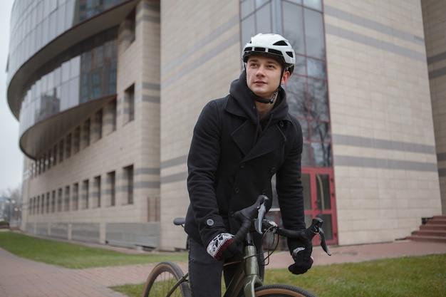 도시의 거리를 사이클링하는 동안 자전거 헬멧을 착용하는 젊은 남자