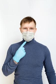 Молодой человек в синих медицинских резиновых перчатках и медицинской маске указывает на его лицо на белом фоне