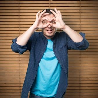 Giovane uomo che indossa un vestito blu. facendo occhiali gesto.