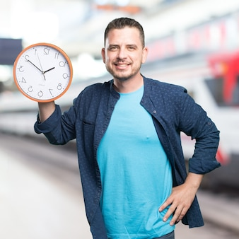 Young man wearing a blue outfit. holding a clock. smiling.
