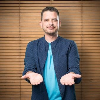 Giovane uomo che indossa un vestito blu. tenendo gesto.
