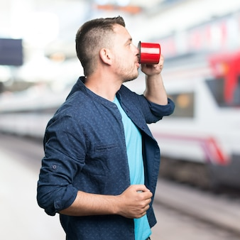 Young man wearing a blue outfit. holding a red cup. showing prof