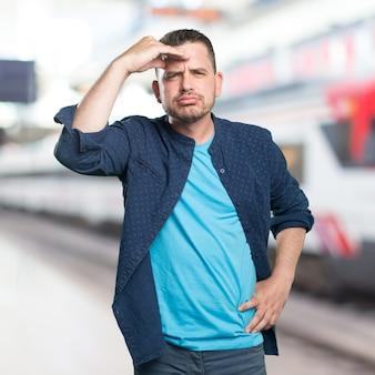 Giovane uomo che indossa un vestito blu. guardando stanco.
