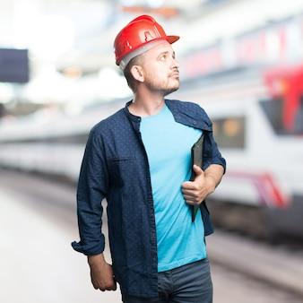 Giovane uomo che indossa un vestito blu. indossare il casco rosso. cercando di
