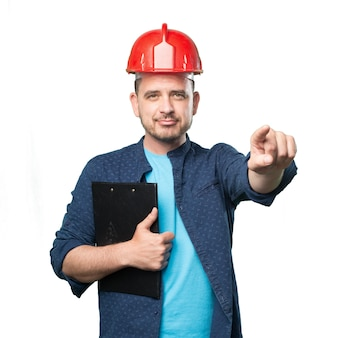 Young man wearing a blue outfit. wearing red helmet. pointing to
