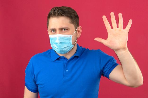 Молодой человек в синей рубашке поло в медицинской защитной маске делает приветственный жест рукой, размахивая рукой, стоя над изолированной розовой стеной