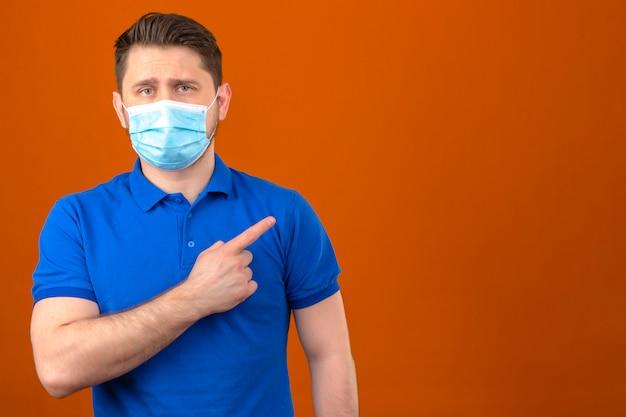 Молодой человек в синей рубашке поло в медицинской защитной маске, указывая пальцем в сторону, стоит над изолированной оранжевой стеной