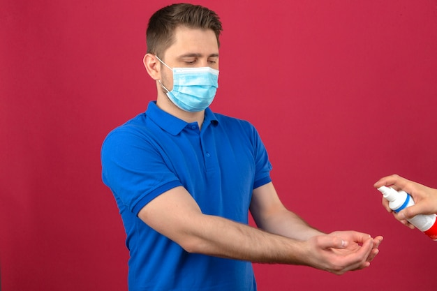 孤立したピンクの壁に彼の手を消毒する消毒剤のために彼の手を伸ばして医療防護マスクで青いポロシャツを着ている若い男