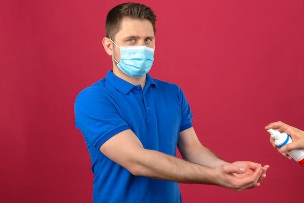 Молодой человек в синей рубашке поло в медицинской защитной маске протягивает руки для дезинфекции дезинфицирующего средства над изолированной розовой стеной