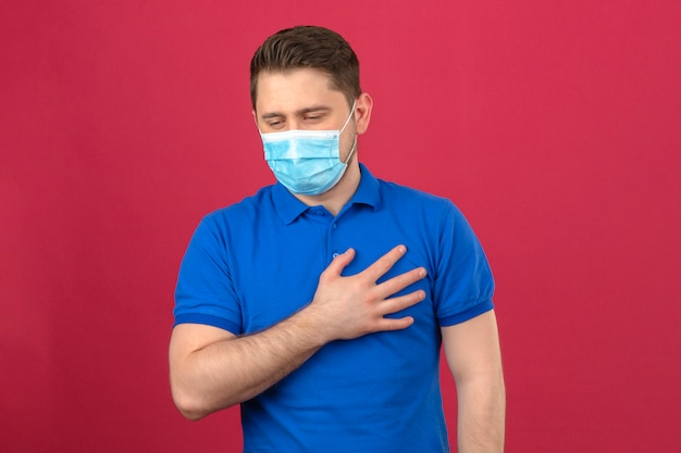 Young man wearing blue polo shirt in medical protective mask holding his hand on chest lungs feeling bad standing over isolated pink wall
