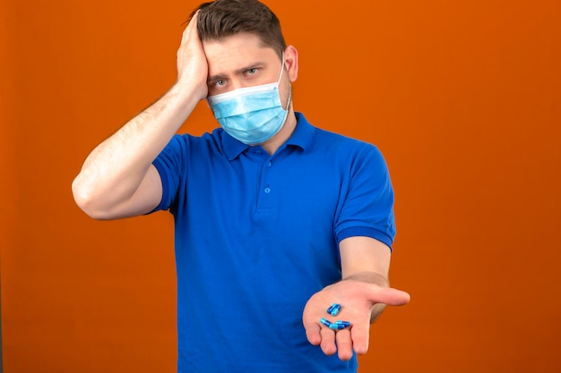 Young man wearing blue polo shirt in medical protective mask looking unwell and sick standing with hand on head suffering from headache holding peels in open hand over isolated orange wall