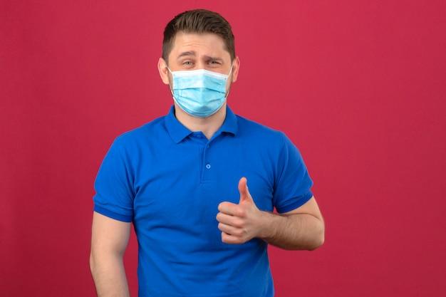 Giovane che porta la camicia di polo blu nella maschera protettiva medica che sorride allegramente mostrando pollice su sopra la parete rosa isolata
